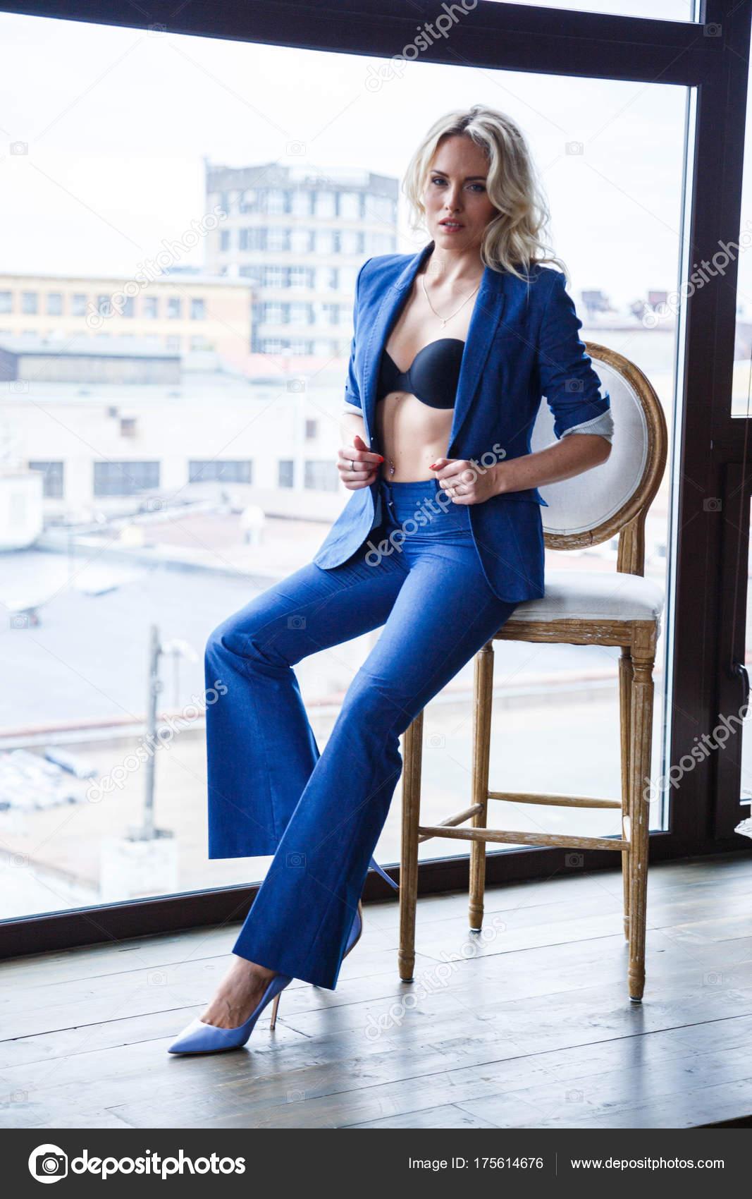 9c5dc083b29 Studio πορτρέτο του όμορφη ξανθιά γυναίκα με σγουρά μαλλιά και κομψό  μακιγιάζ, φοράει το μπλε κοστούμι casual και μπλε παπούτσια σε υψηλούς  λόφους, ...