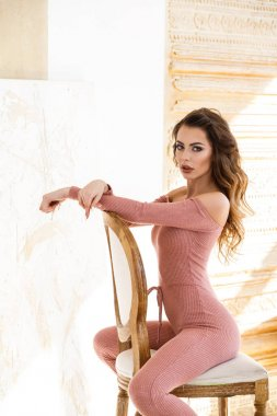 beautiful brunette woman in sexy pink clothes posing in bright interior