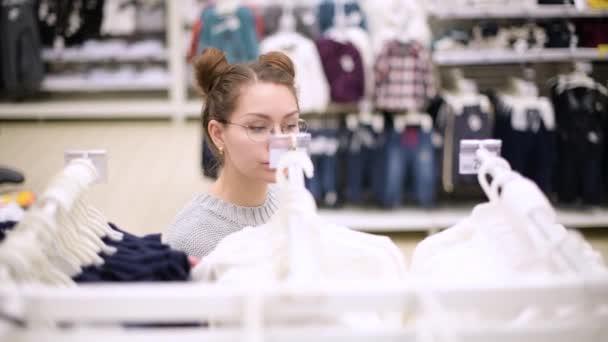 mladá matka kráčí podél řady dětských šatů, vybírá svetr pro své dítě v supermarketu