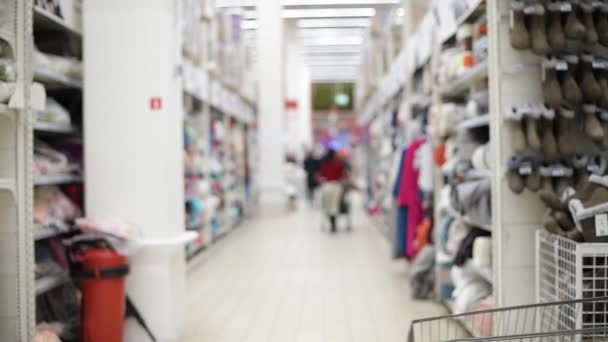 junge Frau mit Kind im Einkaufswagen läuft durch den Supermarkt und sucht das richtige Produkt