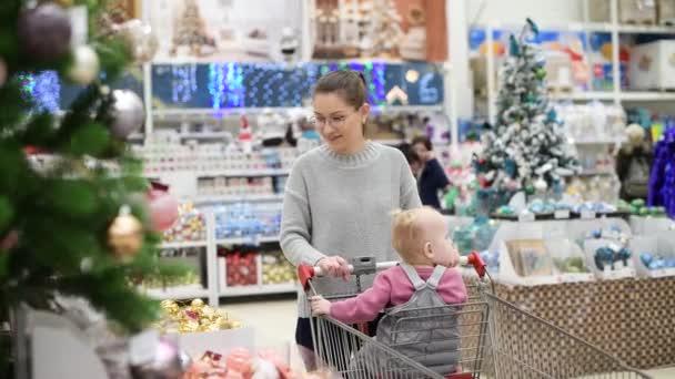 junge Mutter mit kleiner Tochter spazieren in der Abteilung für Neujahrsdekoration und wählen Dekorationen für den Weihnachtsbaum
