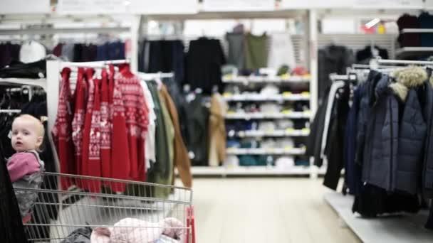 junge Mutter mit kleiner Tochter im Einkaufswagen läuft in der Bekleidungsabteilung eines Supermarktes