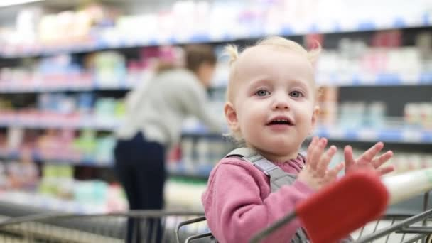kleines Mädchen sitzt in einem Einkaufswagen und wartet darauf, dass Mama im Supermarkt Lebensmittel auswählt