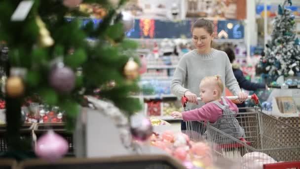 ein Mädchen und ein kleines Kind kaufen Spielzeug für einen Weihnachtsbaum im Supermarkt, selektiver Fokus