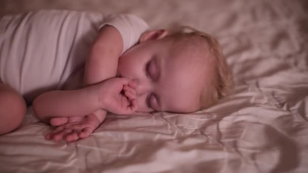 little girl sleeping on bed with a finger in her mouth