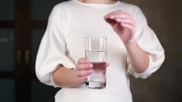 Mädchen wirft lösliche Brausetabletten in ein Glas mit Wasser, ohne Gesicht, Nahaufnahme