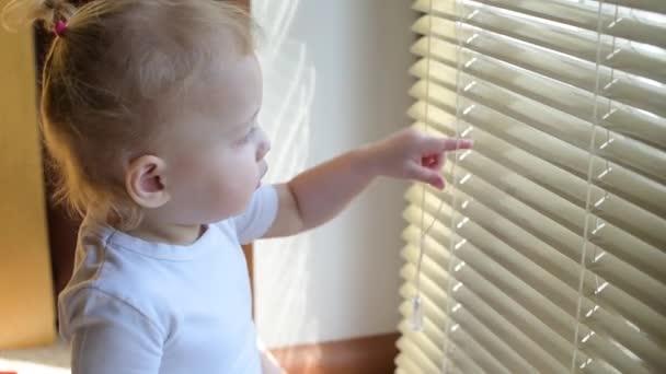 postranní pohled na holčičku, jak se dívá z okna skrz žaluzie. Dítě čekající na něco nebo na někoho. Možná to dítě čeká na rodiče ve školce.