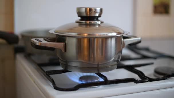 rýže se vaří na plynovém sporáku a zpod zavřeného víka vytéká voda. Hostitelka zapomněla na to, že se vaří jídlo na kamnech