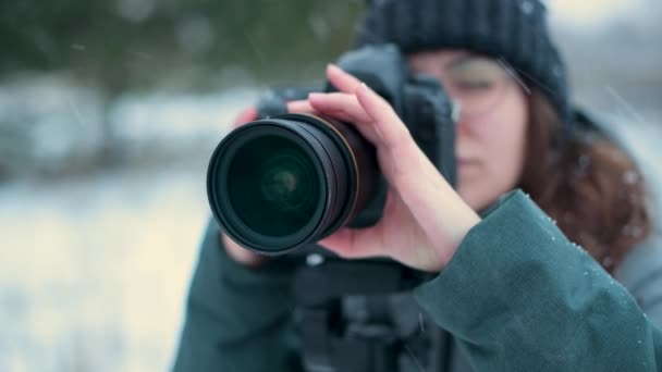 girl photographer takes a picture of landscape outdoors on a winter day. Selective focusing on the lens