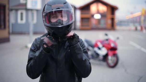 Mladý usměvavý motorkář si sundá helmu na pozadí své motorky večer na parkovišti