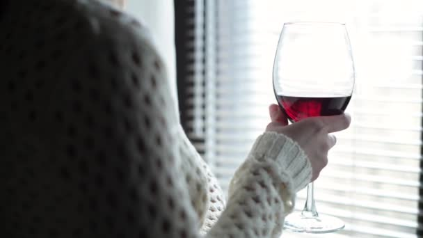 a large wine glass with red wine in the hands of a girl who stands in front of the window