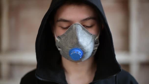 Ein Teenager mit Atemschutzmaske blickt nach unten, hebt dann die Augen und blickt in die Kamera. Nahaufnahme