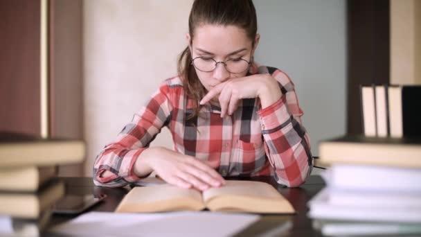 A szemüveges lány edz, egy könyvekkel teli asztalnál ül. Vizsgaelőkészítő ülés. Távolság, levelezés oktatás. Karantén és önizoláció