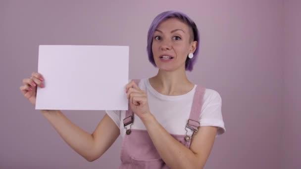 Mladá žena překvapena tím, že ukazuje nějaké informace na bílém prkně, portrét izolovaný na růžovém pozadí