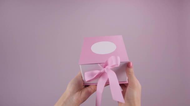 Üres ajándékdobozt pakolok ki. Női kéz fogja és nyitja ajándék rózsaszín háttér. Rossz ajándék koncepció. Ajándék nélküli lány az ünnepeken