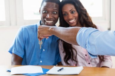 Happy african american couple gets the key for new home