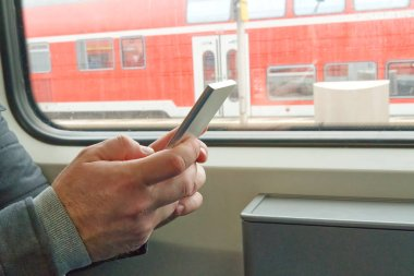 close up man's hands using cellphone at train