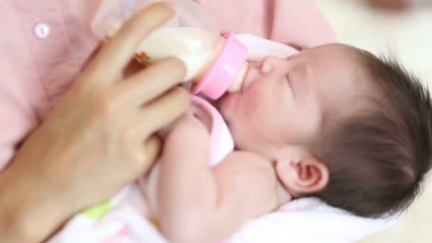 Newborn eating milk from bottle.