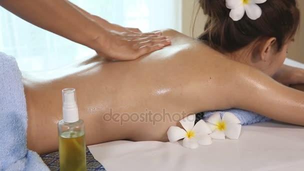 Mladá žena se thajská masáž ve wellness místnosti.