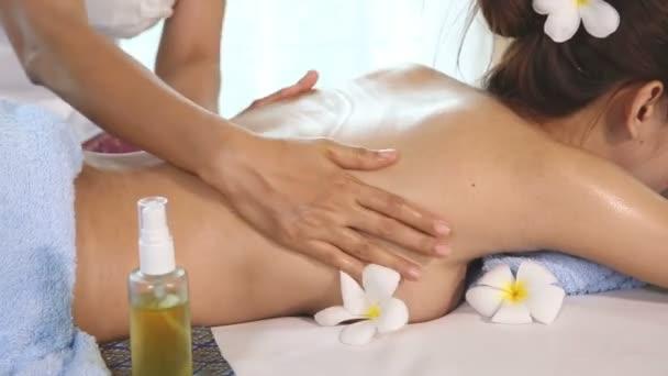 junge Frau bekommt thailändische Körpermassage im Wellnessbereich.