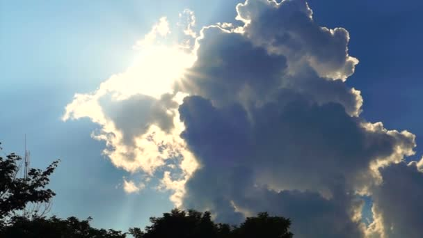 Bright sun beams rays showing behind big white cloud on blue sky background