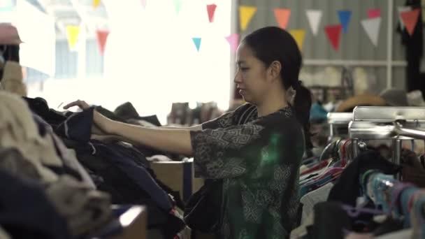 f73a25466bc727 Asiatische Mischlinge Frau einkaufen zweite Kleidung am Flohmarkt Lager–  Stock-Filmmaterial