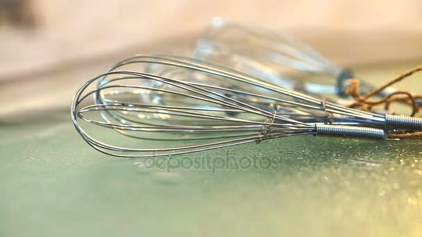 Stainless steel Whisks laying on glass table in modern cooking kitchen