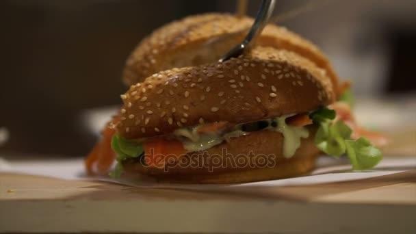 Řezací uzený losos burger v sezamové bulce