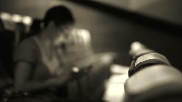 Černobílý záběr rozostření Smíšené rasy dívka pomocí mobilní v kině