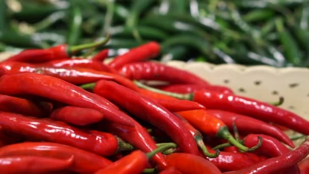 Red and green chili peppers selling in supermarket different basket