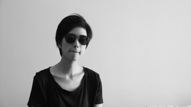 Jihovýchodní Asie dívka, která nosí sluneční brýle pohybující se tělo spolu s písní v její byt černobílý záběr