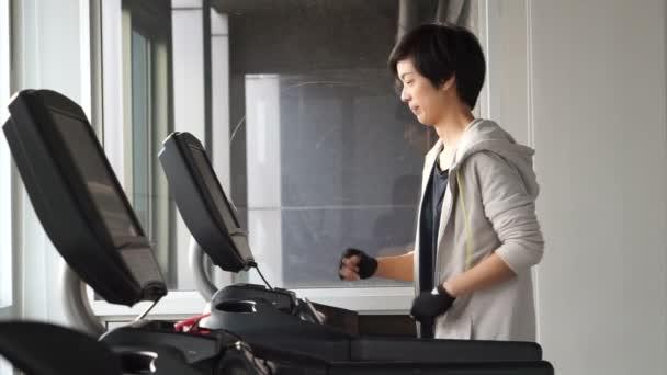Asiatische Mischlinge sportliche Frau Joggen auf dem Laufband im Fitnessstudio, Bewegung und Fitness-Konzept
