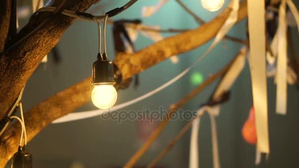 Festival-Glühbirnen hängen mit Bändern an Ast