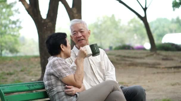 Slow motion šťastný asijské starší pár sedí a pití, restaurace, kavárny v ranní parku. Bavit a projevování lásky