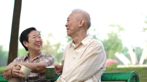 Zpomalený pohyb asijské důchodci pár mluvit a pití kávy v ranní venkovní park