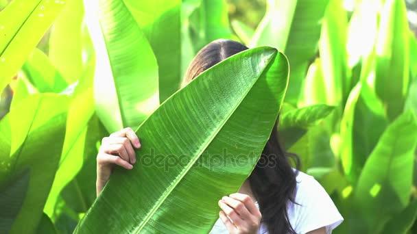 Asijské žena skrývá její výraz za tropické listy. Tajné odhalí koncept