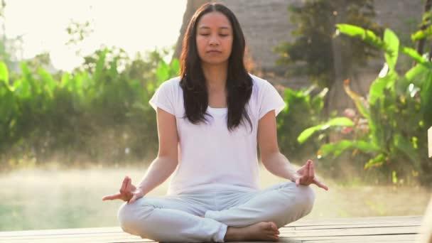 Ázsiai nő ül és nem meditáció reggel köd resort és wellness medence