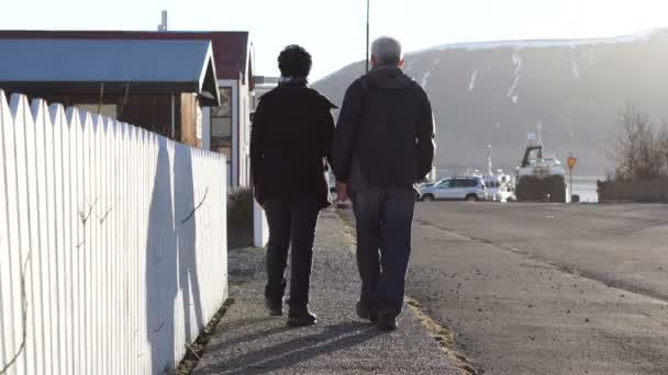 Asian senior couple walking together in Europe trip. Morning sun and house white fence