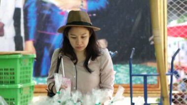 Asian woman smiling wearing hat at local farmer market area. Looking and picking fresh organic vegetable