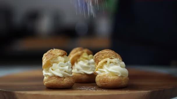 Pékség péksütemény chef locsolás őrölt cukor choux tejszín puff fából készült táblán 4k