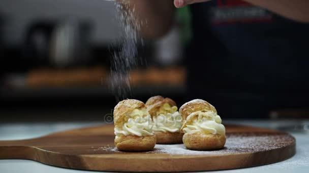 Pekárna cukrář postřikování práškového cukru choux plyšáka na dřevěné desce 4k
