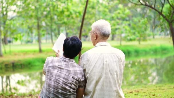 Asijské starší pár čtení knih v parku. Strávit kvalitní čas a nikdy se Nepřestávejte učit něco nového