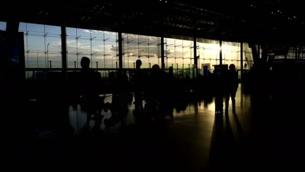 Crowd of people silhouette walking contrast with morning sun light glass architecture at airport
