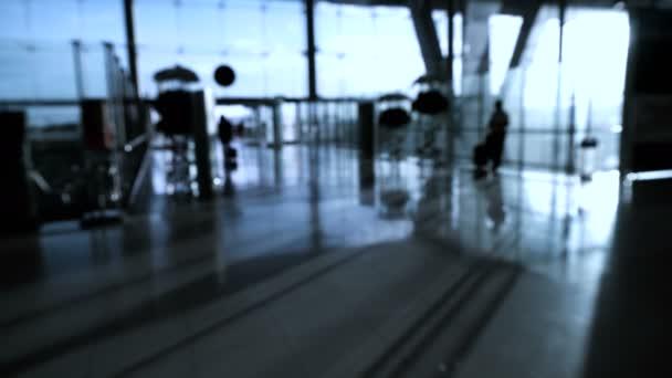 Blur tömeg az emberek sziluettje, gyaloglás üveg szerkezet és a napkelte háttérrel repülőtéren. Absztrakt üzleti és utazó