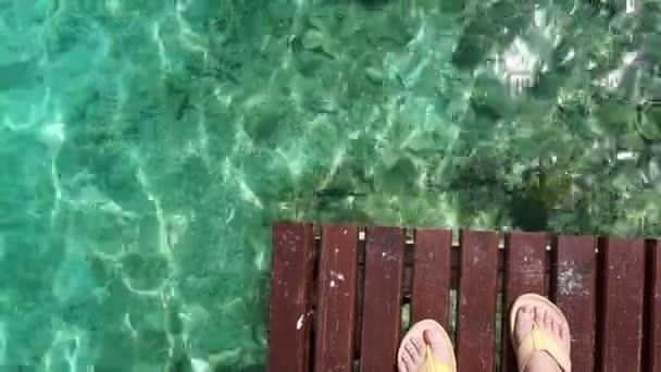 Nohy s deskou žluté sandály pohled přes dřevěné paluby a turqoise oceán moře