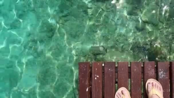 Láb felső sárga szandál Nézd fa fedélzet és türkiz óceán tenger felett