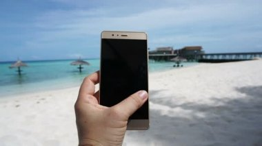POV shot of a smart phone taking photo in tourist hand. Having fun at ocean vacation