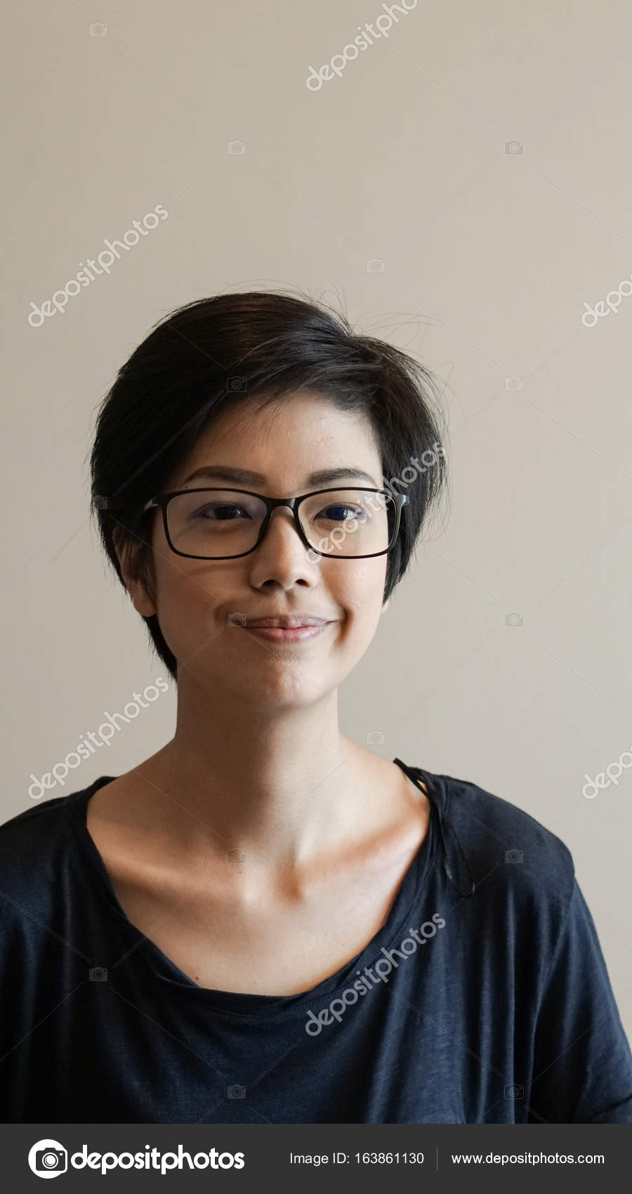 Asian Woman With Short Hair And Glasses On Color Background
