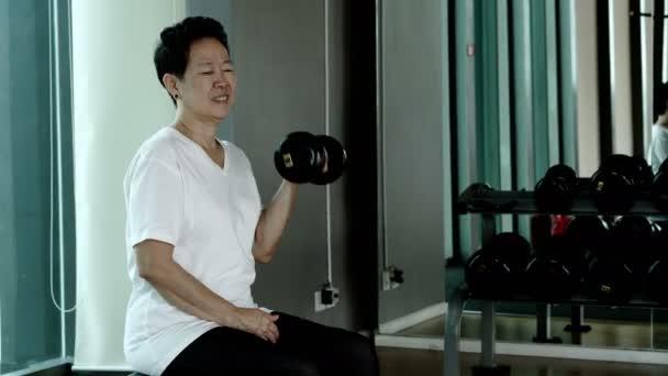 Asijské starší žena zvedání činek, zdravé cvičení v posilovně