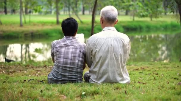 Asijské starší pár střílel z opět sedí v parku, čtení knihy dohromady